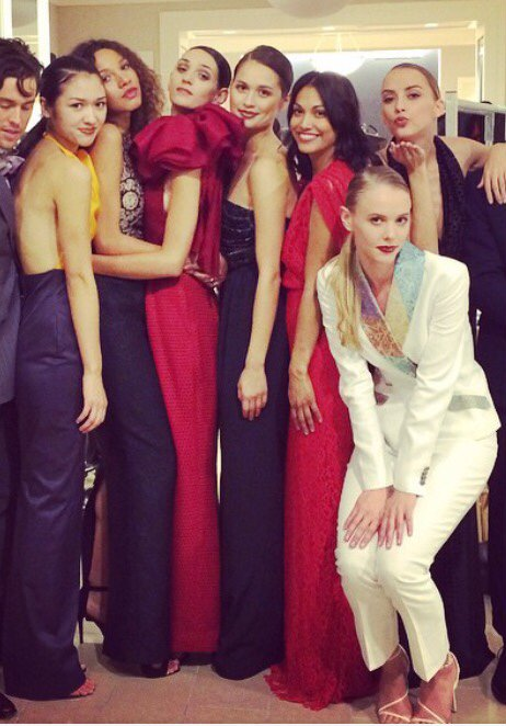 A group of models wearing gowns and a tuxedo in reds, blacks, eggplant and white and seen also with a model wearing Carolina Herrera and Ferragamo for a runway show featuring Angelina Haole couture Carolina Herrera and Ferragamo