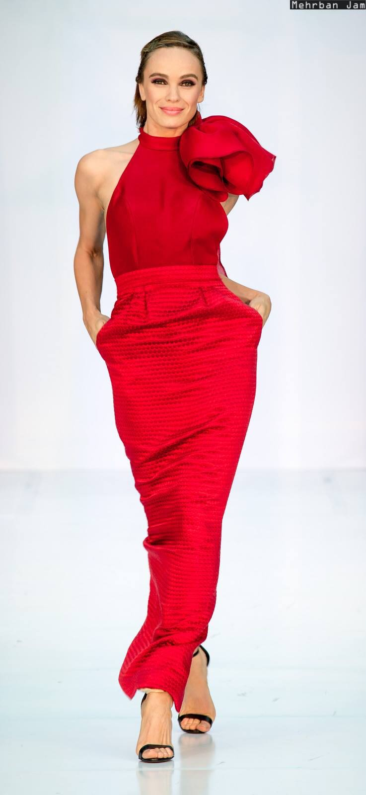 A model walks hands in pockets in center frame toward viewer wearing a red column shaped evening gown in silk organza and brocade by couture fashion designer Angelina Haole