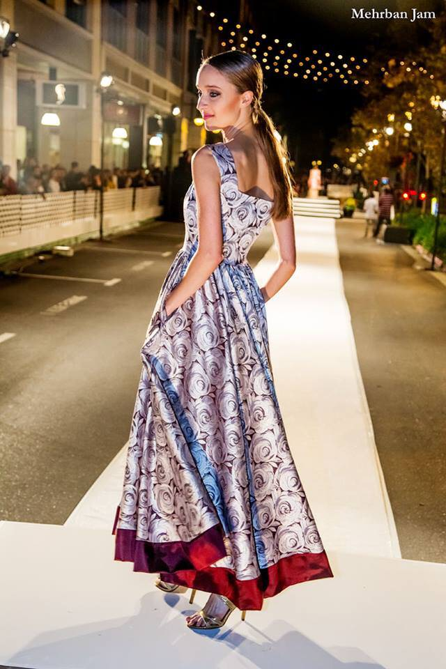 a model turns away from the viewer center frame with her hands in her pockets as she turns, her ankle length dress moving behind her on the runway for Vogue Fashion's night out by Angelina Haole designer wedding and evening couture