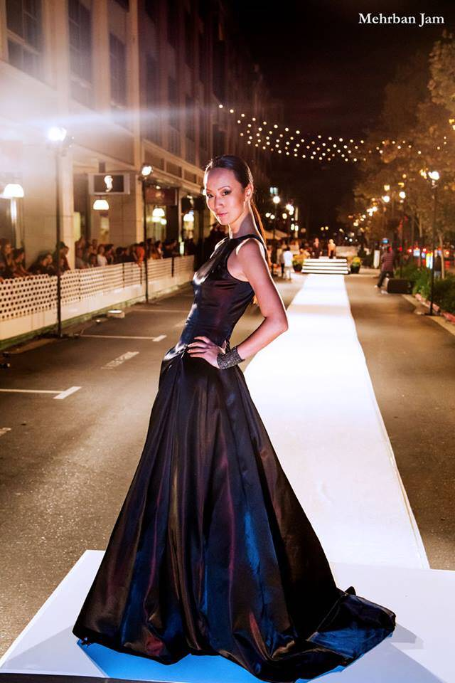 A model stands hands on hips with her side to the viewer and looking at the viewer Vogue fashion night out runway visibile in the background by Angelina Haole Couture designer