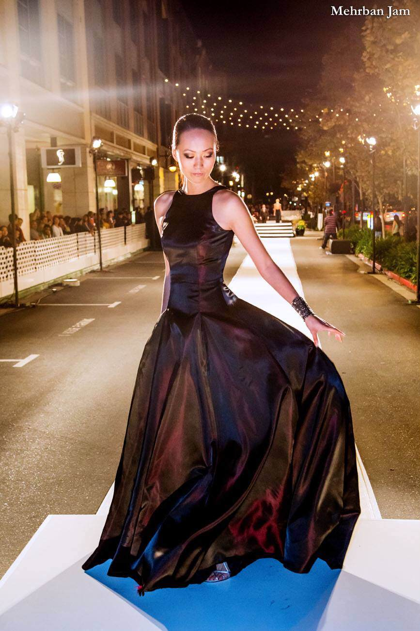 A model stands center frame with slicked back hair a bold black cuff bracelet and an oxblood floor length evening gown flying from her hand as she turns at the end of a runway for Vogue Fashion Night Out dress by couture designer Angelina Haole