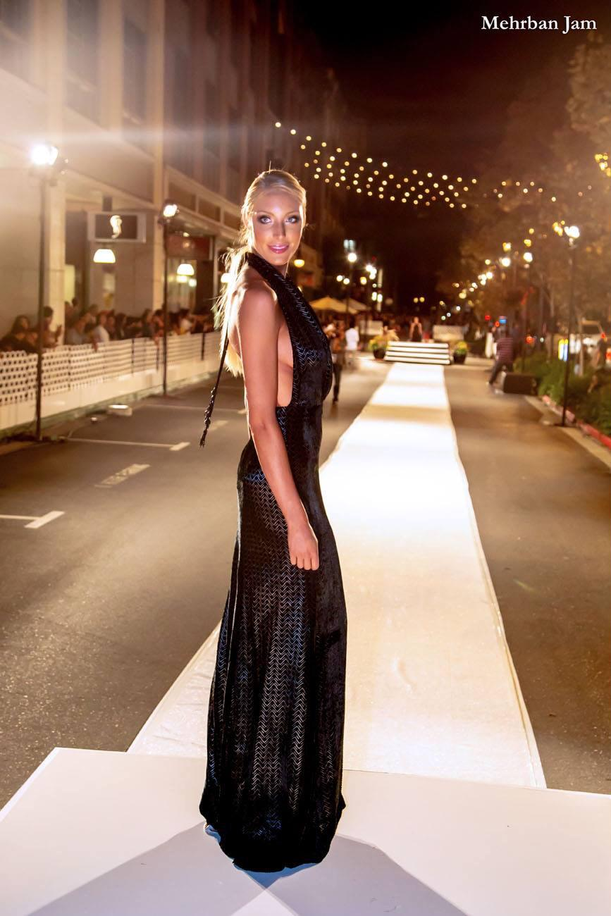 A model stands center frame wearing a column shaped backless halter evening gown turned toward the side and looking toward the viewer the runway visible in the background for Vogue Fashion's Night out by designer Angelina Haole