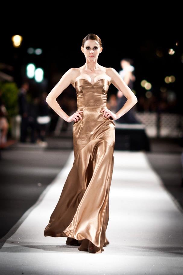 A model walks the Vogue Fashion's night out runway center frame with her hands on her hips and wearing a bronze strapless evening gown in silk by designer Angelina Haole Verona Italy