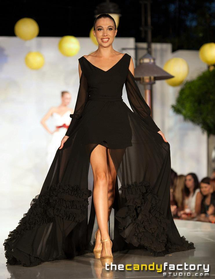 A smiling model walks toward the viewer wearing a bold black evening dress floor length with a slit by couture gown designer Angelina Haole