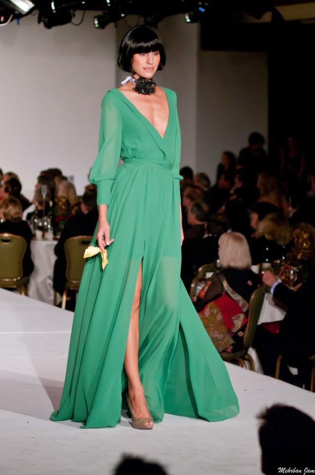 A model is seen walking a runway wearing a green flowing floor length evening gown with a deep v neckline and a high slit by couture gown designer Angelina Haole