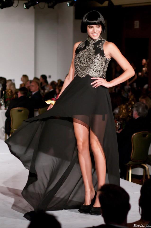 A model is seen turning and spinning her gown showing her legs and her high low evening gown in black and metallic green on the runway by couture designer Angelina Haole
