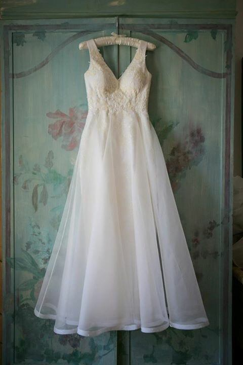 An off white wedding dress made in silks and organza and delicately embroidered hangs from the door of a green armoire hand painted with pink flowers