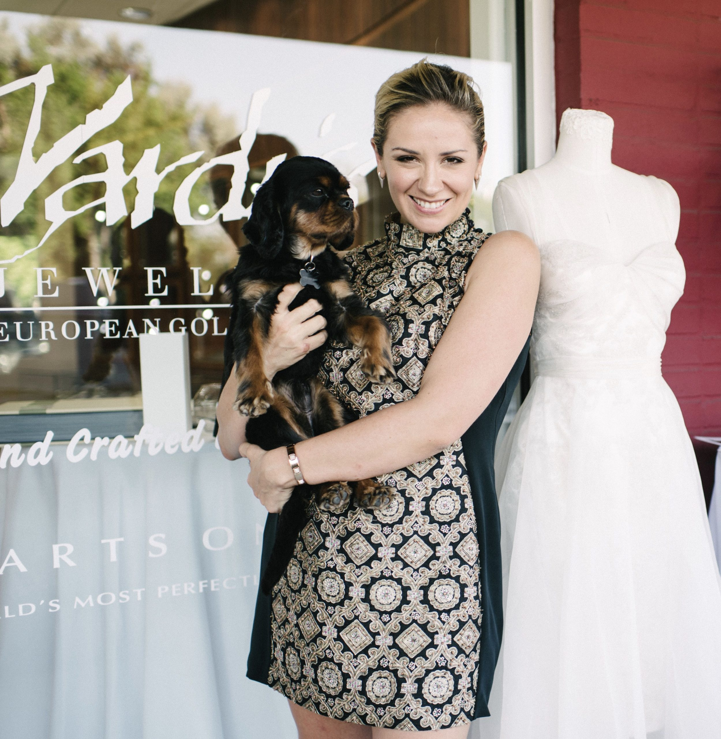 Designer Angelina Haole holding a black cavalier king charles spaniel in front of a jewelry store and standing next to a wedding dress on display
