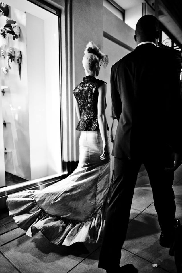 A model is seen from behind wearing a billowing skirt that follows her as she walks and a the back of a man is visible to her right seen walking gown by couture designer Angelina Haole