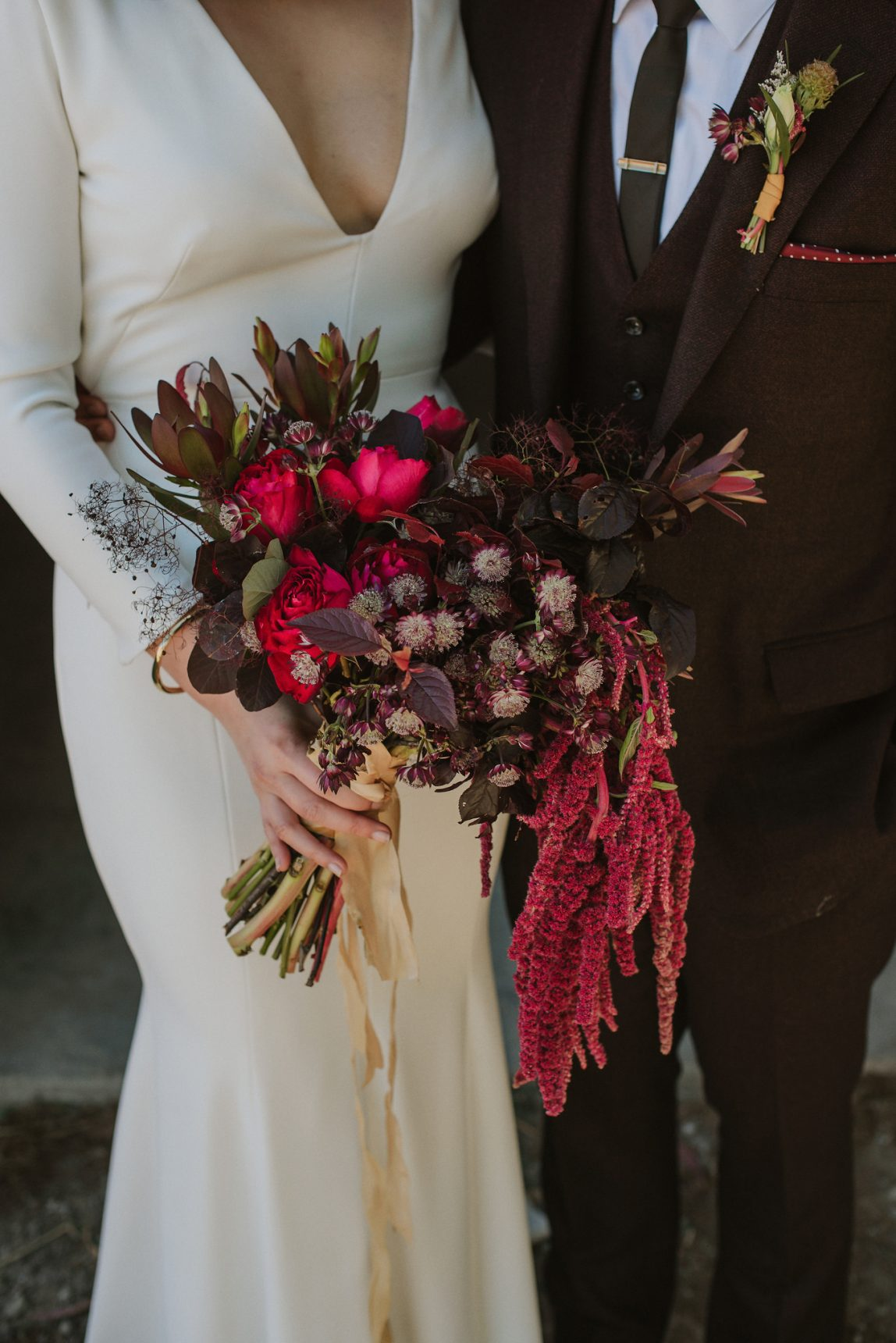 close up photo of wedding bouqet in dark greens and reds with a bride and groom barely visible behind, dress by couture wedding dress designer Angelina Haole Verona Italy