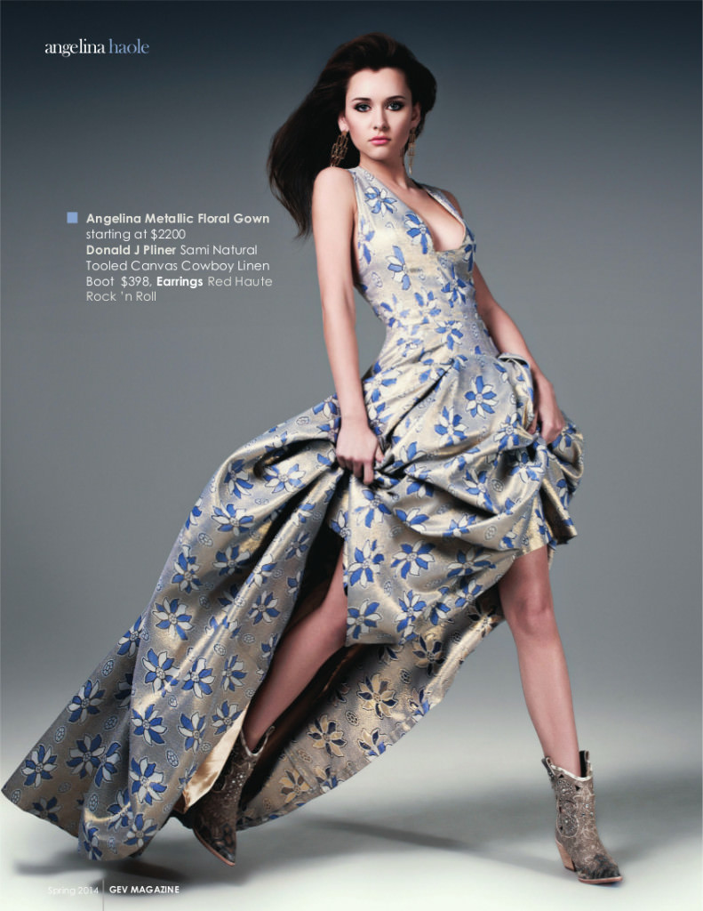 A model is seen jumping forward holding the skirt of her evening gown above her knees so her legs and boots are visible gown in blue and gold by couture designer Angelina Haole for a magazine spread