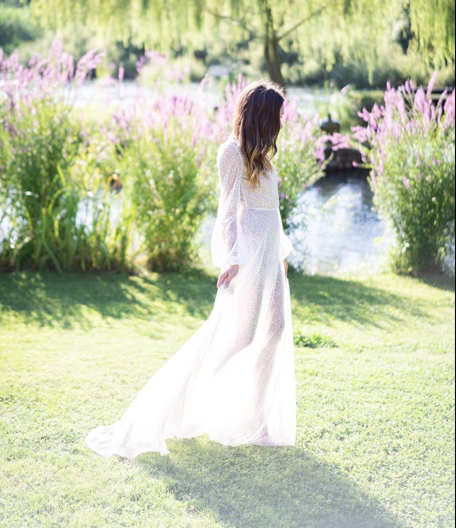 A bride in a wedding gown seen from the side as she walks toward the left of the image on grass with a lake and flowers in the background dress by wedding dress designer Angelina Haole Italy
