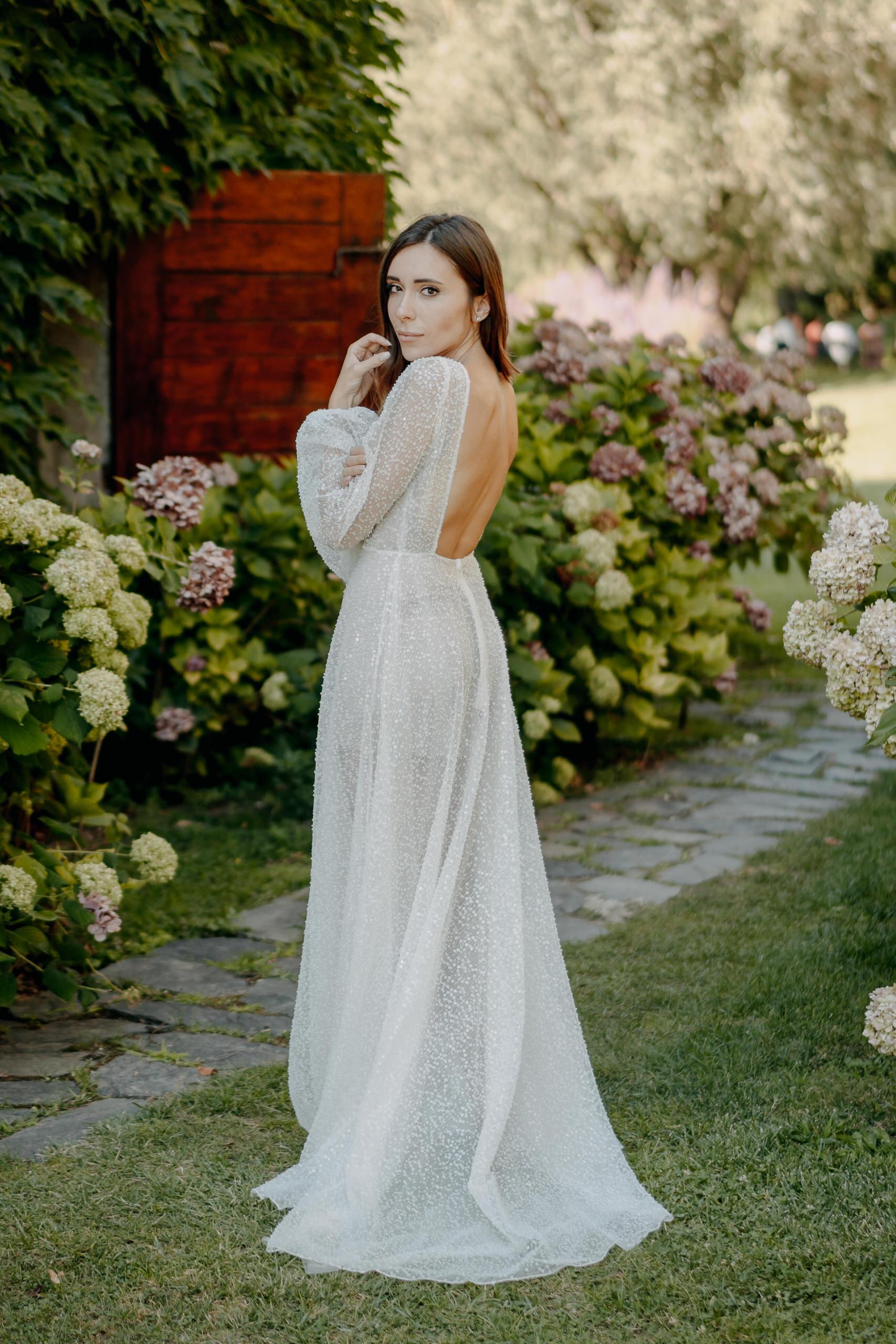 Sposa in abito da sposa senza schienale rivolto verso lo spettatore alzando la mano al mento su uno sfondo di fiori a Vicenza Italia Abito di Angelina Haole Verona